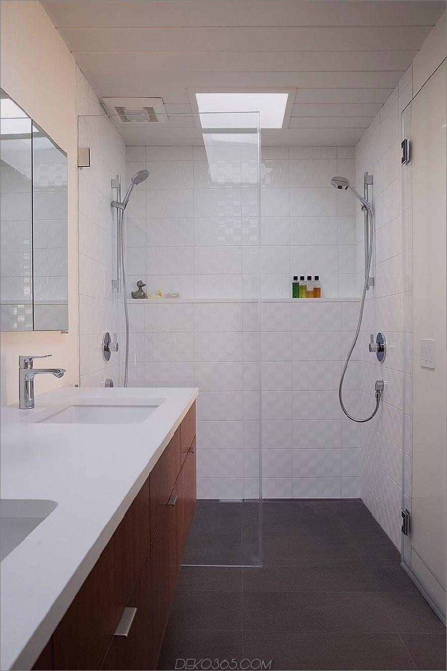 Das Badezimmer ist mit strukturierten weißen Fliesen ausgestattet, während die Eitelkeit aus Holz das Hauptthema widerspiegelt