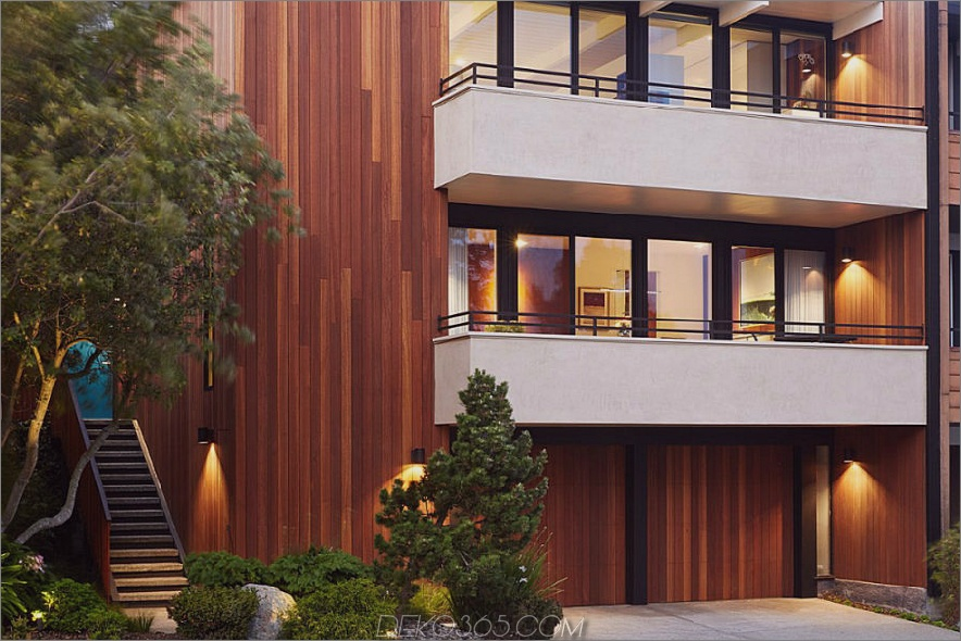 Die Straßenfassade ist mit Holzpaneelen und weißen Balkonen verkleidet
