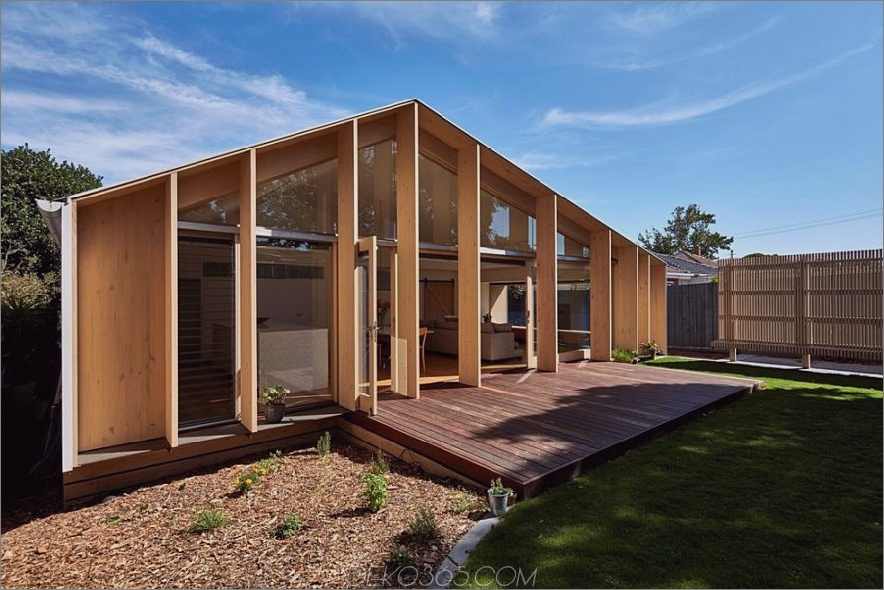 Eine angrenzende Holzterrasse schafft Platz im Freien neben einer grünen Wiese