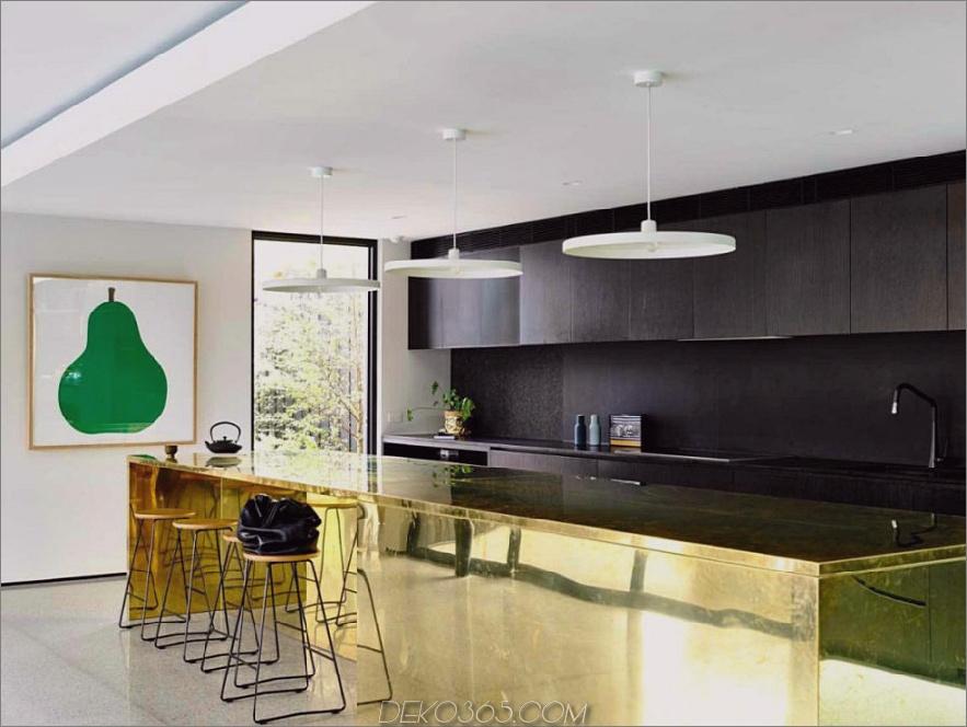 Moderne Küche mit schwarzen Schränken und goldener Kücheninsel