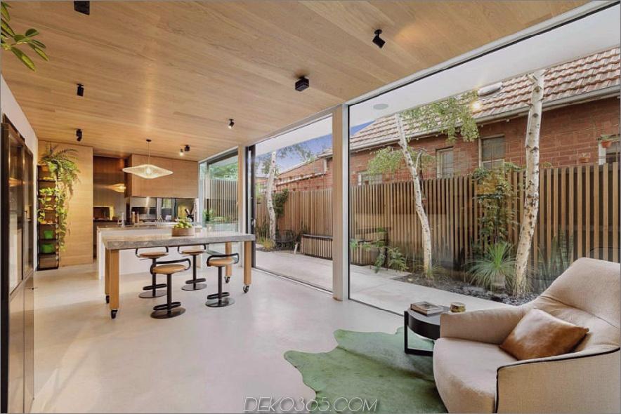 Küche und Essbereich teilen sich dank Glasschiebewänden optisch den Raum mit dem Hinterhof