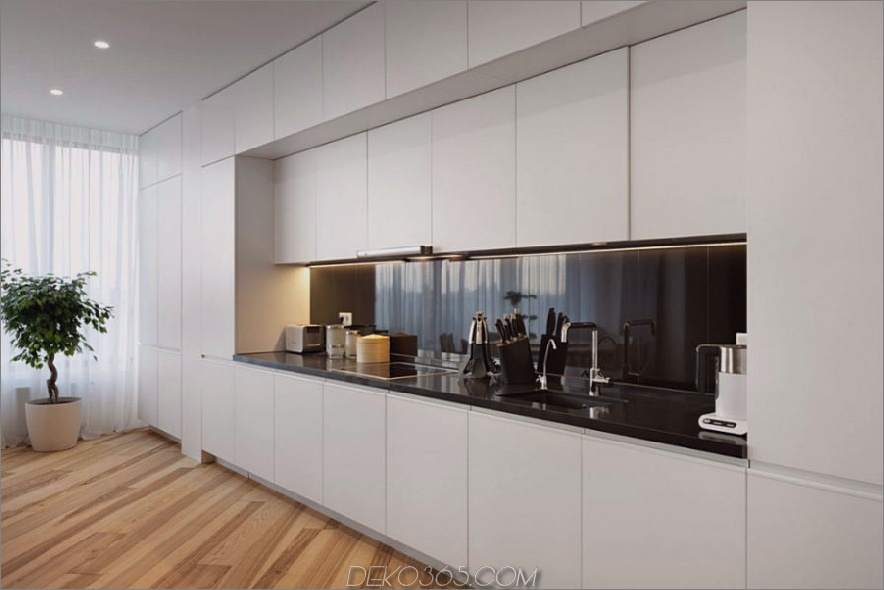 Schwarze Arbeitsplatte und Backsplash setzen einen Kontrast zur weißen Küche
