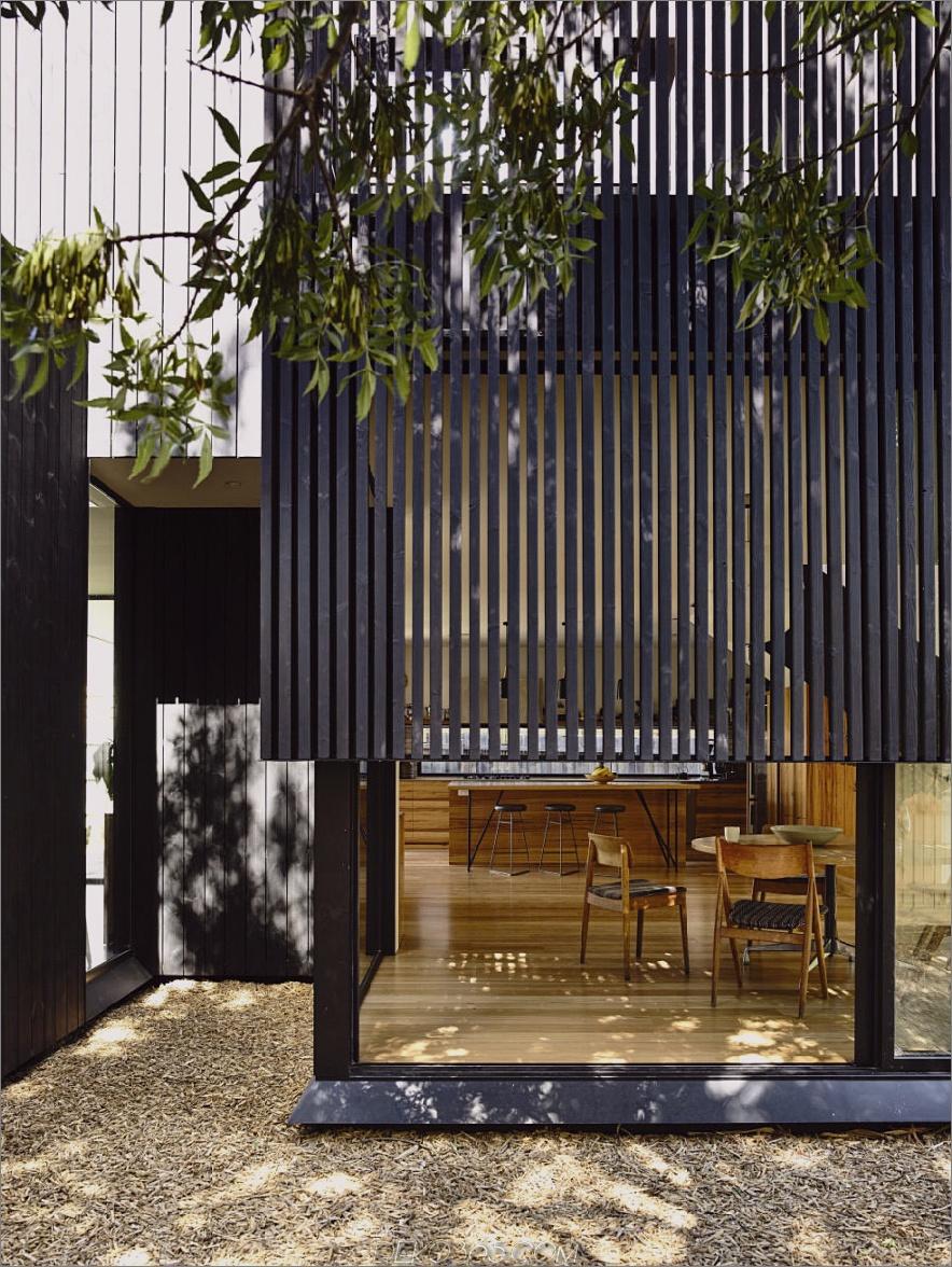 Die Glasmerkmale des Hauses erhalten Licht und Privatsphäre durch die Holzschicht