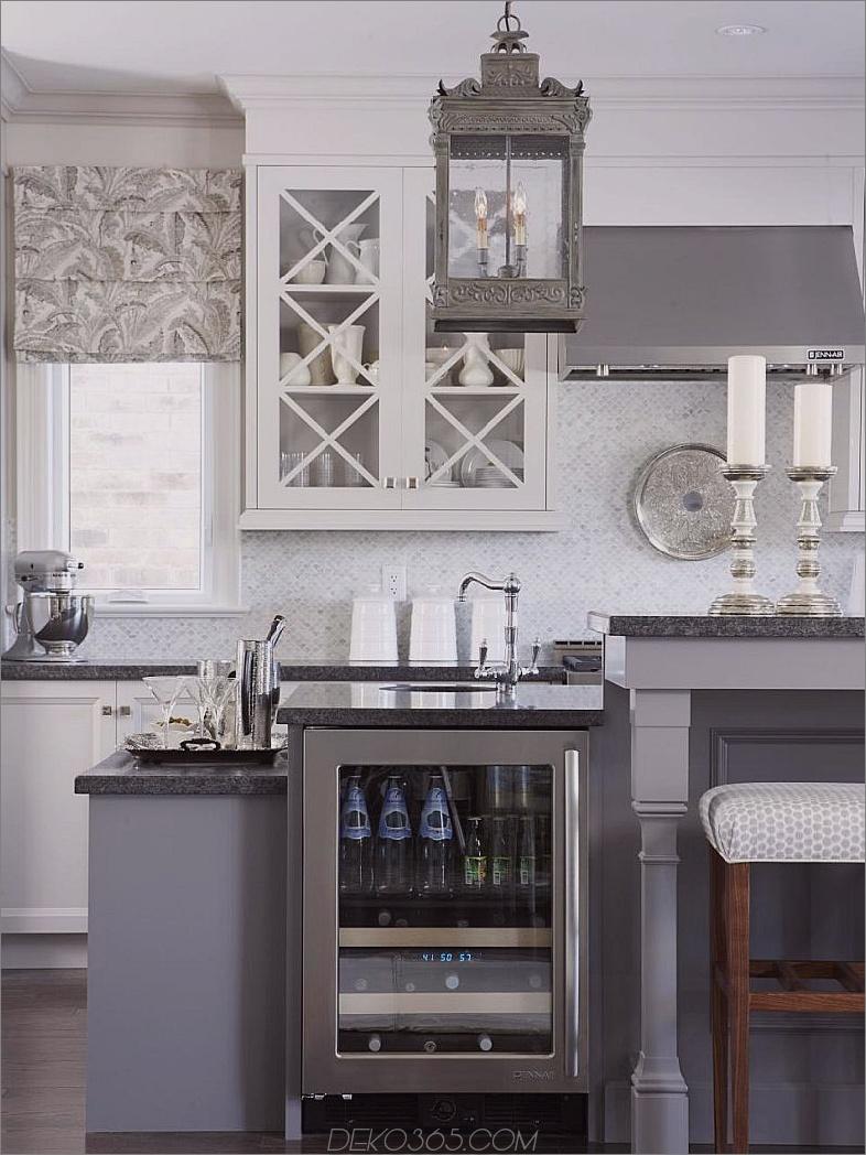 Graue Küche mit geschliffenen Granit-Arbeitsplatten und Carrara-Marmor-Backsplash