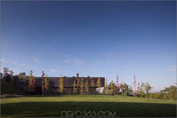 black-home-with-bright-interior-eingebaut in grasige hügelseite-4-side.jpg