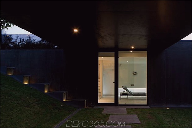 black-home-with-bright-interior-eingebaut in grasige hügelseite-8-courtyard-door.jpg