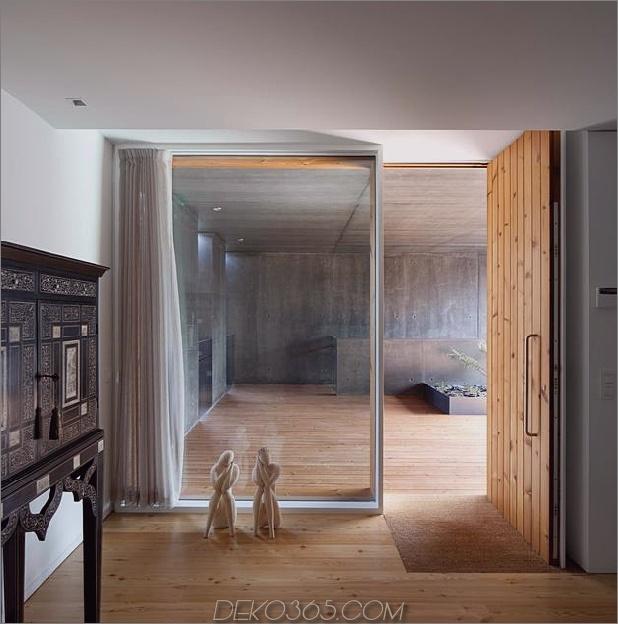 black-home-with-bright-interior-eingebaut in grasige hügelseite-17-inside-entrance.jpg